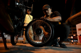 Malaysian sidewalk mechanic helping people by roadside