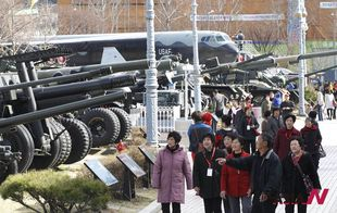 Visitors pass by weapons at Korea War Memorial Museum as tensions escalate between the two Koreas