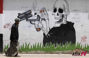 A Yemeni man passes anti-smoking graffiti on World Health Day