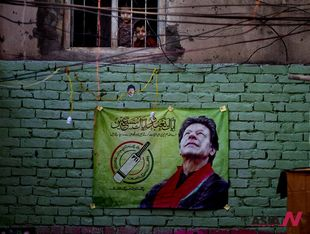 Pakistani opposition leader's election campaign poster hung on wall