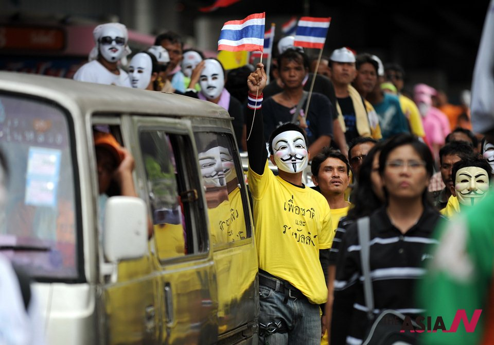 Thais wearing white masks participate in anti-gov't protest