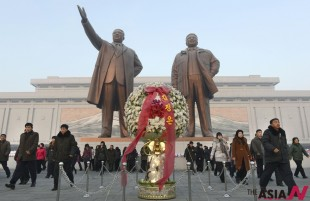 North Koreans visit Mansu Hill to pay their respects at the base of statues of the late leaders Kim Il Sung, left, and Kim Jong Il in Pyongyang, North Korea, Tuesday, Dec. 17, 2013, on the second anniversary of the death of Kim Jong Il. (AP/NEWSis)