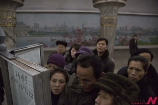 North Korean subway commuters gather around a public newspaper stand on the train platform in Pyongyang, North Korea on Friday, Dec. 13, 2013 to read the headlines about Jang Song Thaek, North Korean leader Kim Jong Un's uncle who was executed as a traitor. (AP/NEWSis)