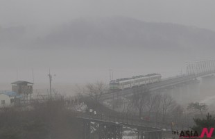 A train runs on the rail track, which the two Koreas hope to reconnect as part of an agreement reached in 2000, in the fog at the Imjingak Pavilion near the border village of Panmunjom, which has separated the two Koreas since the Korean War, in Paju, South Korea, Saturday, Jan. 25, 2014. North Korea on Friday agreed to resume reunions of families separated by the 1950-53 Korean War, the latest in a series of conciliatory gestures from a country that was threatening South Korea and the U.S. with nuclear war almost a year ago.(AP/NEWSis)