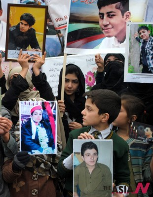 Students hold photographs of  fellow students who were killed during an attack by Taliban gunmen on Army Public  School (APS) during a protest in northwest Pakistan's Peshawar on Feb. 7, 2015. (Photo : Xinhua)