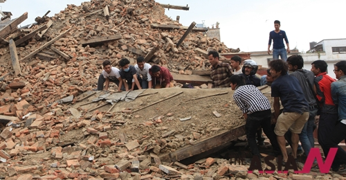 In this April 25, 2015 photo, people try to lift the debris from a temple at Hanumandhoka Durbar Square after an earthquake in Kathmandu, capital of Nepal, Saturday, April 25, 2015. A strong earthquake shook Nepal's capital and the densely populated Kathmandu Valley before noon Saturday, causing extensive damage with toppled walls and collapsed buildings, officials said.