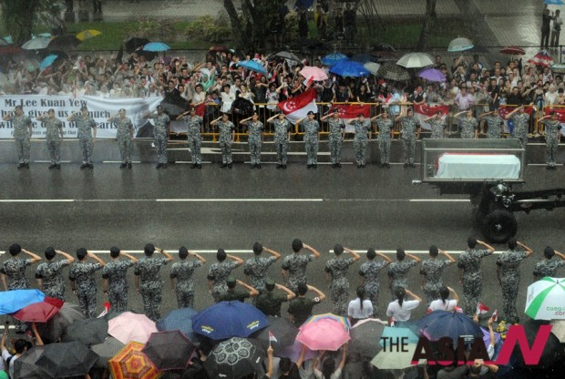 Singaporeans gather along the street as a military gun carriage conveying the coffin of Singapore's founding father Lee Kuan Yew passes by in Singapore, March 29, 2015. (Photo : Xinhua)