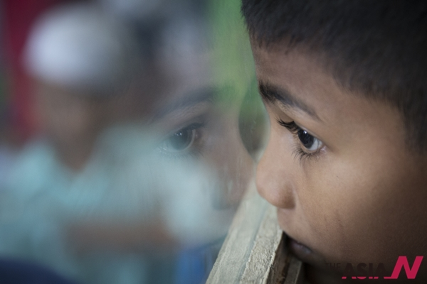 In this May 21, 2015 photo, Sadhussin Mohamad, 6, a Rohingya schoolboy, watches teacher day celebrations outside his classroom  at a Rohingya Education Center in Klang, Malaysia. With more work opportunities than Indonesia and a more Muslim-friendly environment than Thailand, Malaysia has long been the destination of choice for Rohingya Muslims fleeing persecution in Myanmar.