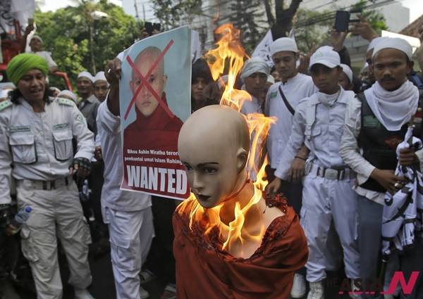 Indonesian Muslim protesters burn a mannequin representing Myanmar's radical Buddhist monk Ashin Wirathu during a protest demanding an end to the violence against ethnic Rohingyas in Rakhine State, outside the Embassy of Myanmar in Jakarta, Indonesia, Wednesday, May 27, 2015. In the last three years, hundreds of minority Rohingya Muslims have been killed and hundreds of thousands others others are now living under apartheid-like conditions in crowded camps or forced to flee their homes to avoid persecution in Buddhist-majority Myanmar.