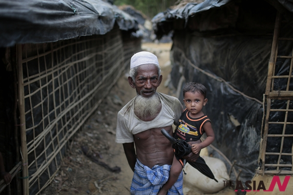 In this Thursday, May 21, 2015 photo, an elderly Rohingya Muslim man carries his grandson as they walk in an alley at a camp for Rohingya people in Ukhiya, near Cox's Bazar, a southern coastal district about, 296 kilometers (183 miles) south of Dhaka, Bangladesh. As a boat people crisis emerged in Southeast Asia in recent weeks, nearly all the focus has been on the Rohingya: the persecuted Muslim minority fleeing Myanmar. But of the more than 3,000 people who have come ashore this month in Indonesia, Malaysia and Thailand, about half were from Bangladesh, according to the U.N. refugee agency, mainly poor laborers seeking better jobs and a brighter future.