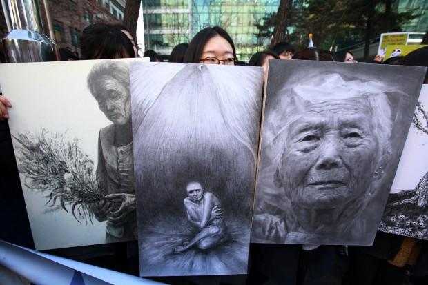 Supporters of former South Korean comfort women, who were forced to serve for the Japanese Army as sex slaves during World War II, hold pictures during a rally against Japan's revision on teaching manuals in Seoul, South Korea, Jan. 29, 2014. (Xinhua)