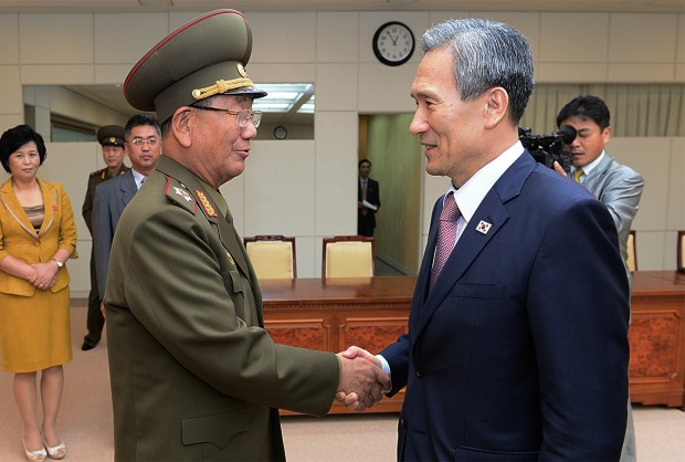 In this photo provided by the South Korean Unification Ministry, South Korean presidential security adviser Kim Kwan-jin, right, shakes hands with Hwang Pyong So, North Korea's top political officer for the Korean People's Army, after their meeting at the border village of Panmunjom in Paju, South Korea, Tuesday, Aug. 25, 2015. (The South Korean Unification Ministry via AP)