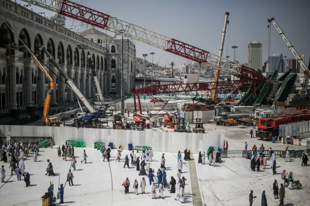 Muslim Pilgrims walk past the site of a crane collapse that killed over a hundred Friday at the Grand Mosque in the holy city of Mecca, Saudi Arabia, Tuesday, Sept. 15, 2015. Saudi Arabia has in part blamed the construction giant Saudi Binladin Group for the collapse last week of a crane at Mecca that killed more than 100 people and injured over 350 ahead of the hajj. (AP Photo/Mosa'ab Elshamy)