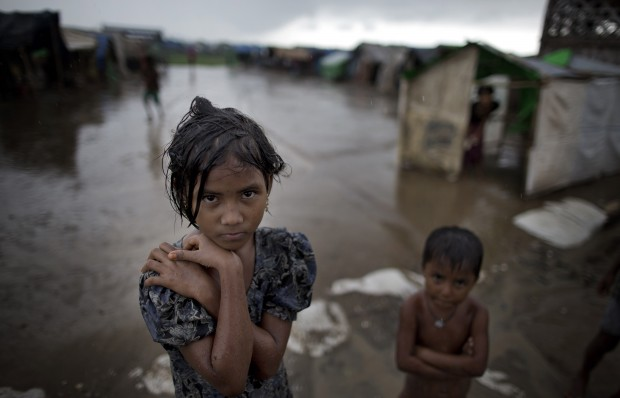 In this June 26, 2014 photo, a girl, self-identified as Rohingya, stands close to her family's tent house at Dar Paing camp for refugees, suburbs of Sittwe, Western Rakhine state, Myanmar. Suu Kyi's many supporters overseas have been dismayed by her silence over the plight of the Rohingya, a Muslim minority who have faced decades of persecution and have only been treated worse since the end of the junta. Rohingya were allowed to vote in 2010, but are being denied in 2015 from voting.(AP Photo/Gemunu Amarasinghe)