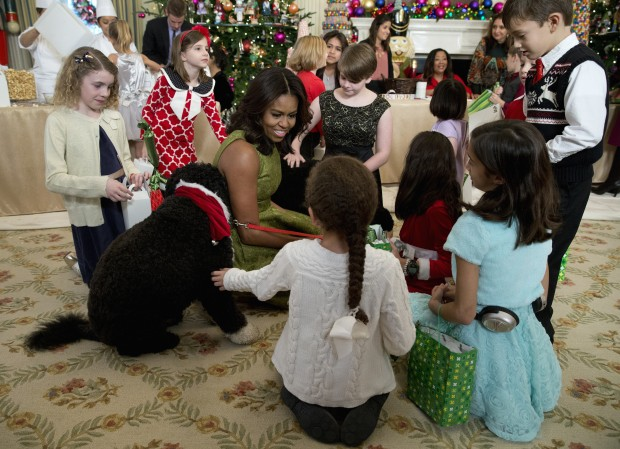 First lady Michelle Obama with dogs Bo, left, and Sunny, behind at right, are surrounded by children in the State Dining Room of the White House in Washington, Wednesday, Dec. 2, 2015, where they made holiday crafts and treats during a preview of the 2015 White House holiday decor. (AP Photo/Carolyn Kaster)