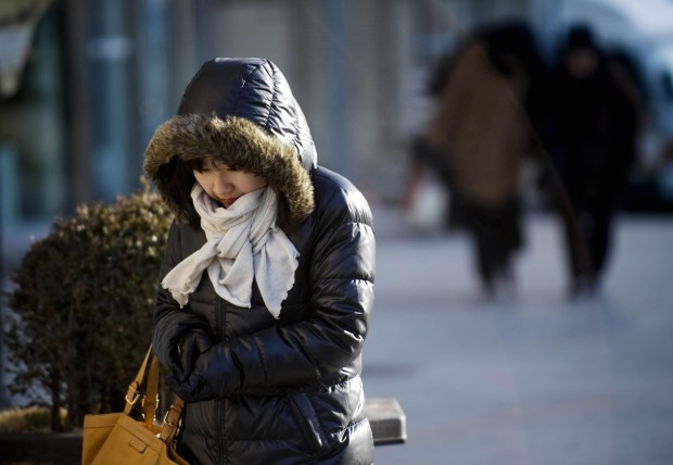 A woman wearing heavy clothes walks on a street in Seoul, capital of South Korea, as they counter the coldest winter. (Xinhua/Lui Siu Wai)