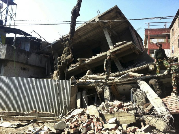 Indian soldiers inspect a house that collapsed in an earthquake in Imphal, capital of the northeastern Indian state of Manipur, Monday, Jan. 4, 2016. A 6.7 magnitude earthquake hit India's remote northeast region before dawn on Monday. (AP Photo/Worshon Ngashangva)