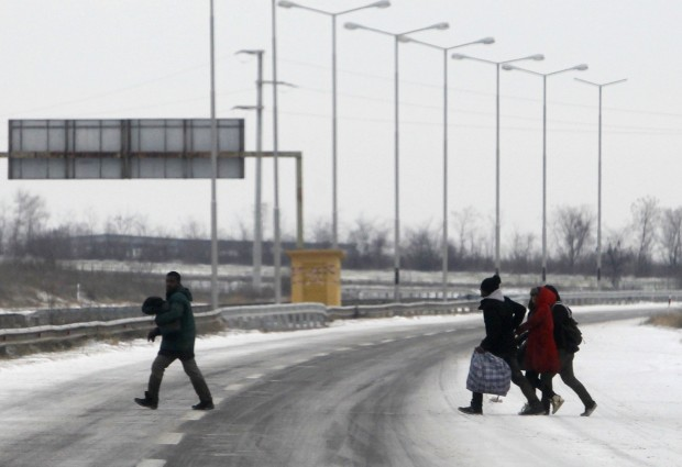 A group of migrants cross snow covered road in northern Macedonia, near the border with Serbia, on their way north to more prosperous European Union countries, Monday, Jan. 4, 2016. Denmark and Sweden tightened their borders on Monday in efforts to stem the flow of migrants entering Scandinavia from Germany. (AP Photo/Boris Grdanoski)