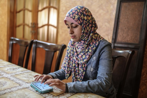 Palestinian college student Israa Al-ashqar ,23, works on an application on her mobile phone. (Xinhua/Wissam Nassar)