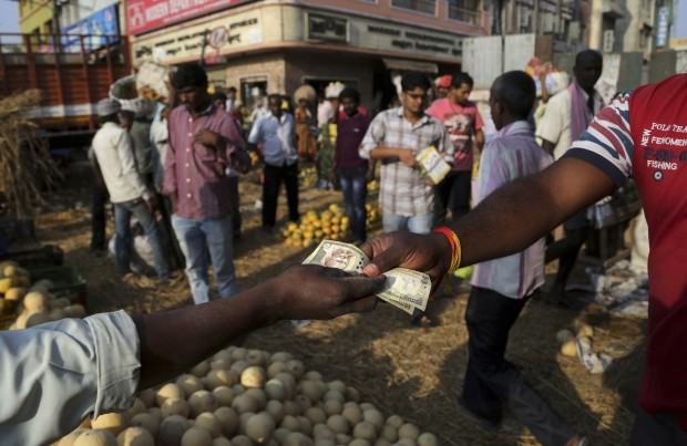 People trade at a wholesale fruit market in Bangalore, India, Monday, Feb. 29, 2016. India has pledged to invest billions of dollars to improve the lives of farmers and boost the rural economy, boost consumer demand and stimulate growth. (AP Photo/Aijaz Rahi)