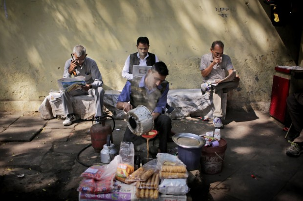 An Indian roadside tea vendor prepares tea for people reading newspapers in New Delhi, India, Tuesday, March 1, 2016. On Monday, Finance Minister Arun Jaitely announced a massive scheme to provide cooking gas in 15 million poor households across rural India, a step that could save millions of trees that would otherwise have been cut for fuel. (AP Photo/Altaf Qadri)