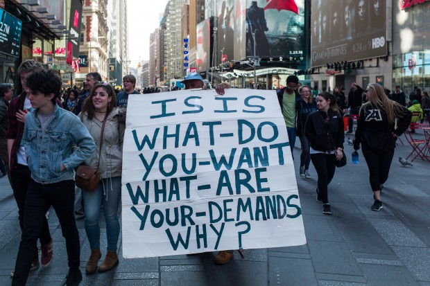 A man holds a sign as he protests ISIS at New York's Time Square, the United States, March 22, 2016. The Islamic State (IS) has claimed responsibility for Tuesday's terror attacks in Belgian capital of Brussels, which killed at least 34 people and injured more than 100. (Xinhua/Li Muzi)