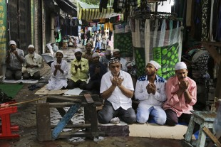 Muslims offer prayers on a pavement on the Friday ahead of Eid al-Adha in Kolkata, India, Friday, Sept. 9, 2016. Muslims around the world celebrate Eid al-Adha, or the Feast of the Sacrifice, by sacrificing animals to commemorate the prophet Ibrahim's faith in being willing to sacrifice his son. (AP Photo/Bikas Das)