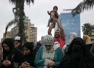 A man holds a child in the air as others pray the dawn Eid al-Adha prayers at Mustafa Mahmoud Square in Cairo, Egypt, Monday, Sept. 12, 2016. (AP Photo/Thomas Hartwell)