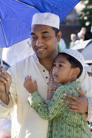 A man holds his son, and an umbrella for shade, during a service for the Eid al-Adha holiday, Monday, Sept. 12, 2016, in the Queens borough of New York. (AP Photo/Mark Lennihan)