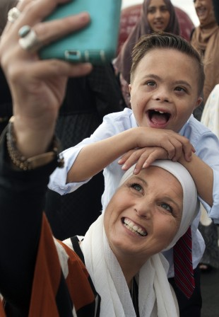 """Kimberly Kaman takes a selfie with her son Reiyan, 12, during Eid al-Adha at Angel Stadium in Anaheim, Calif., on Monday, Sept. 12, 2016. She says the holiday, marking Abraham's willingness to sacrifice his son on God's command, applies to her in a personal way. """"I had to sacrifice my family's wishes over my acceptance of God"""" in the Muslim faith, she says. (Mindy Schauer/The Orange County Register via AP)"""