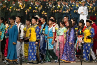 Chinese young people in ethnic minority dress walk to pay respects during a ceremony marking Martyrs' Day at Tiananmen Square in Beijing Friday, Sept. 30, 2016. Chinese President Xi Jinping and other Chinese leaders presented flower baskets and scores of ordinary people filed up to lay a single flower each on Friday at the Monument to the People's Heroes to mark Martyrs' Day. (AP Photo/Mark Schiefelbein)