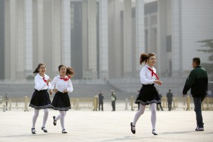 Late-arriving members of Chinese Communist Party's Young Pioneers youth organization run across Tiananmen Square before a ceremony marking Martyrs' Day in Beijing Friday, Sept. 30, 2016. Chinese President Xi Jinping and other Chinese leaders presented flower baskets and scores of ordinary people filed up to lay a single flower each on Friday at the Monument to the People's Heroes to mark Martyrs' Day. (AP Photo/Mark Schiefelbein)