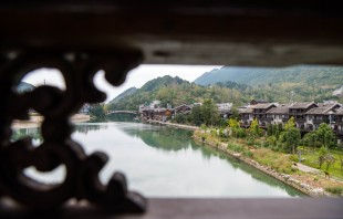 CHONGQING, Sept. 30, 2016 -- Aerial photo taken on Sept. 29, 2016 shows tourists visiting the covered bridge across the Apeng River in southwest China's Chongqing. Those previous wooden buildings covering the bridge were destroyed by fire in 2013, and the bridge reopened one year later after reconstruction. (Xinhua/Liu Chan)