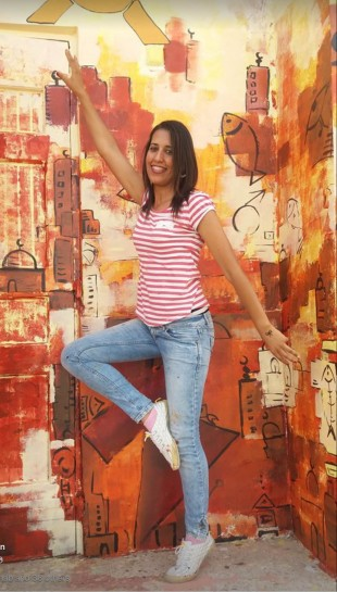 Tunisian artist poses next to her wall artwork