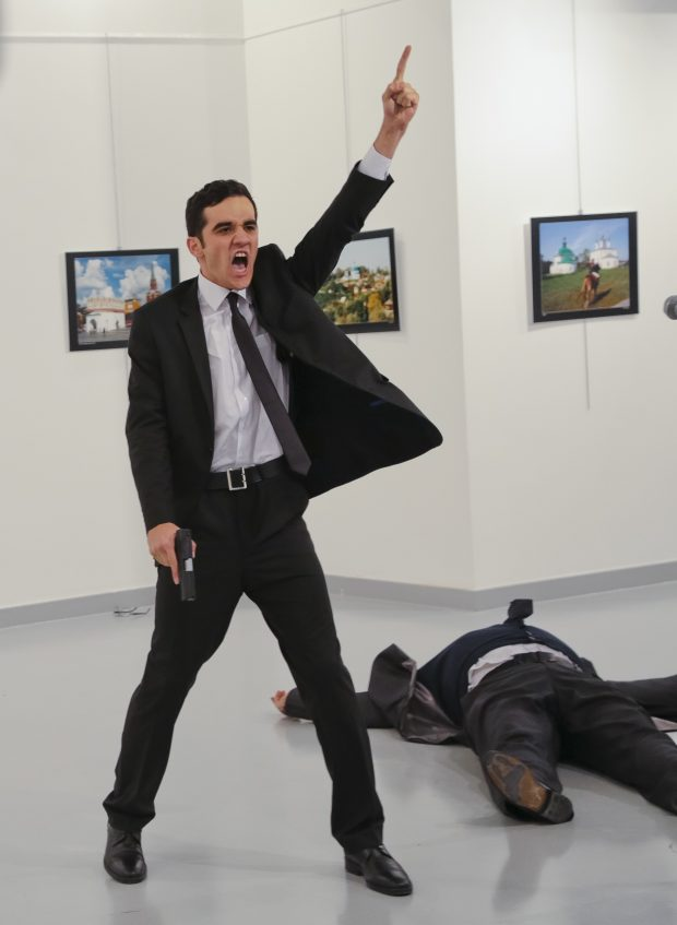"Mevlut Mert Altintas, an off-duty police officer, shouts after shooting Andrei Karlov, right, the Russian ambassador to Turkey, at an art gallery in Ankara, Turkey, on Monday, Dec. 19, 2016. Turkey's president implicated a U.S.-based Muslim cleric in the killing of Russia's envoy to Turkey, saying the policeman who carried out the attack was a member of his ""terror organization."" (AP Photo/Burhan Ozbilici)"