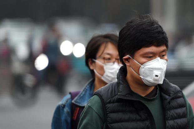 (161018) -- BEIJING, Oct. 18, 2016 (Xinhua) -- Pedestrians wearing masks walk on a street in Beijing, capital of China, Oct. 18, 2016. A yellow alert for air pollution was issued on Tuesday in Beijing. (Xinhua/Ju Huanzong) (zyd)