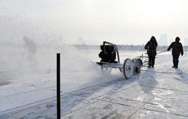 HARBIN, Dec. 5, 2016 (Xinhua) -- People cut ice on the frozen Songhuajiang River in Harbin, capital of northeast China's Heilongjiang Province, Dec. 5, 2016.    (Xinhua/Wang Jianwei) (zwx)