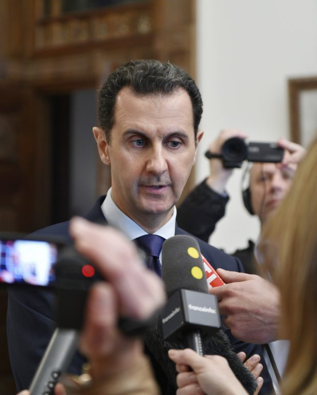 """In this photo released Monday, Jan. 9, 2017 by the Syrian official news agency SANA, Syrian President Bashar Assad, left, speaks with French journalists in Damascus, Syria. Assad said in remarks published on Monday that he was prepared """"to negotiate everything"""" at talks set to begin in later this month in Kazakhstan, seeking to cast himself as a peacemaker after his forces' recapture of Aleppo last month. Assad also defended his troops' deadly bombardment of eastern Aleppo. (SANA via AP))"""