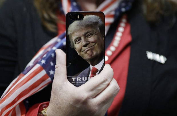 Sept. 29, 2016, file photo, a woman holds up her cell phone before a rally with then presidential candidate Donald Trump in Bedford, N.H. President-elect Trump tweeted Tuesday that North Korea won't develop a nuclear weapon capable of reaching parts of the United States, but it's possible it already has. After five atomic test explosions and a rising number of ballistic missile test launches, many experts believe that North Korea can arm short- and mid-range missiles with warheads that put Guam at risk. (AP Photo/John Locher, File)