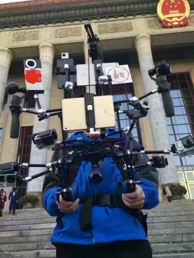 """A reporter with Guangming Online carrying an almost 15-kilogram """"Iron Man"""" multichannel live broadcast cloud platform outside the two sessions. (Photo from WeChat account)"""