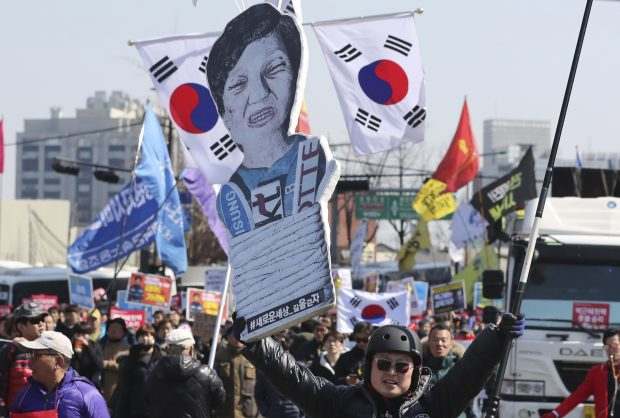 A protester carries a cutout of impeached President Park Geun-hye as they march toward the presidential house in Seoul, South Korea, Friday, March 10, 2017. In a historic ruling Friday, South Korea's Constitutional Court formally removed impeached President Park Geun-hye from office over a corruption scandal that has plunged the country into political turmoil, worsened an already-serious national divide and led to calls for sweeping reforms. (AP Photo/Lee Jin-man)