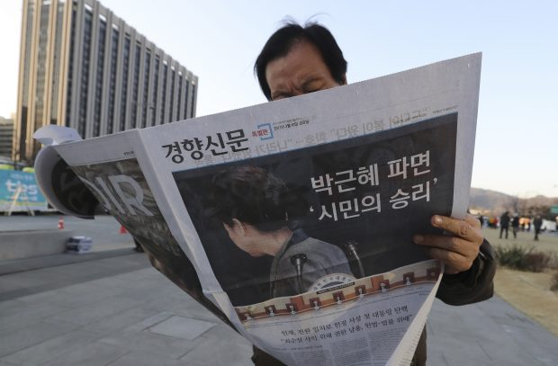 A man reads an extra edition of a newspaper reporting about impeached President Park Geun-hye in Seoul, South Korea, Friday, March 10, 2017. In a historic, unanimous ruling Friday, South Korea's Constitutional Court formally removed impeached President Park Geun-hye from office over a corruption scandal that has plunged the country into political turmoil and worsened an already-serious national divide. (AP Photo/Lee Jin-man)