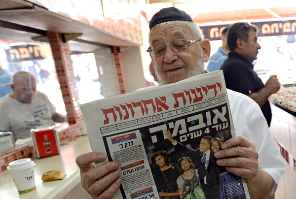 "Image #: 20040951 An Israeli man reads the Hebrew newspaper Yediot Ahronot featuring a photo of US President Barack Obama and his family on the cover and reads in Hebrew ""Obama Four More Years"" at a cafe in Jerusalem, Israel, November 8, 2012. UPI/Debbie Hill /LANDOV"