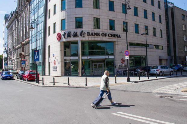 A passerby walking in front of the Poland branch of the Bank of China in Warsaw, the country's capital city. Officially started operation on June 6, 2012, the bank has had full access to the financial market of Poland, providing high-quality financial services for Chinese and Polish clients from the industrial, commercial and financial sectors as well as for individual customers. Its services include deposit, loan, remittance of local and foreign currencies, foreign exchange transactions, trade finance, and guarantee, etc. The branch is the first Chinese bank officially operating in Poland.