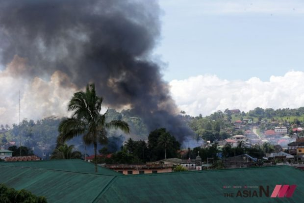 (170602) -- MARAWI CITY, June 2, 2017 (Xinhua) -- Smoke billows from a residential area during an airstrike in Marawi City, Lanao Del Sur Province, the Philippines, June 2, 2017. More elite troops were sent to the besieged Marawi City in the southern Philippines to flush the remaining members of the Maute militant group who are holed up in some parts of the city. (Xinhua/Rouelle Umali) (zcc)