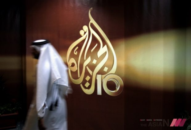 In this Nov. 1, 2006 file photo, a Qatari employee of Al Jazeera Arabic language TV news channel walks past the logo of Al Jazeera in Doha, Qatar. Hackers allegedly broke into the website of Qatar's state-run news agency and published a fake story quoting the ruling emir, authorities there said Wednesday, May 24, 2017, as Saudi Arabia and the United Arab Emirates responded by blocking Qatari media, including broadcaster Al-Jazeera. (Photo : AP / NEWSis)