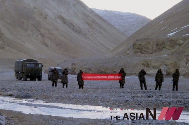 """In this Sunday, May 5, 2013, file photo, Chinese troops hold a banner which reads """"You've crossed the border, please go back"""" in Ladakh, India. China is insisting that India withdraw its troops from a disputed Himalayan plateau before talks can take place to settle the most protracted standoff in recent years between the nuclear-armed neighbors. (Photo : AP/NEWSis)"""