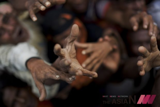 Newly arrived Rohingya stretch out their hands to receive puffed rice food rations donated by local volunteers in Kutupalong, Bangladesh, Saturday, Sept. 9, 2017.  (Photo : AP/NEWSis)