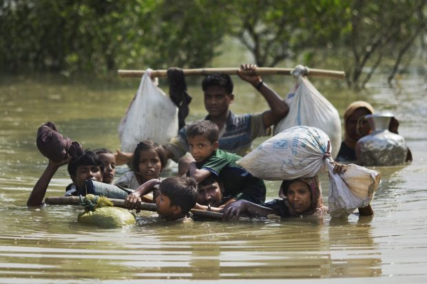 In this Tuesday, Sept. 5, 2017, file photo, a Rohingya family reaches the Bangladesh border after crossing a creek of the Naf river on the border with Myanmmar, in Cox's Bazar's Teknaf area. (AP Photo/Bernat Armangue, File)