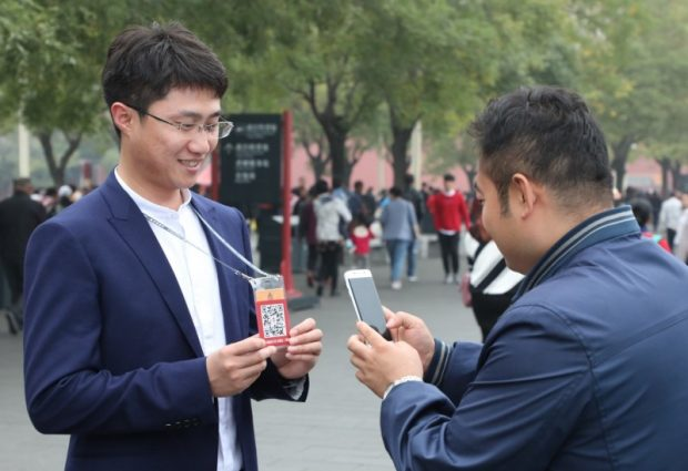 A visitor scans a QR code at the Forbidden City. (Photo from the Palace Museum official website)